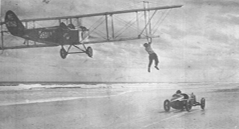 historic photo of plane over beach with man hanging off wing of plane.