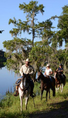people horseback riding along the water